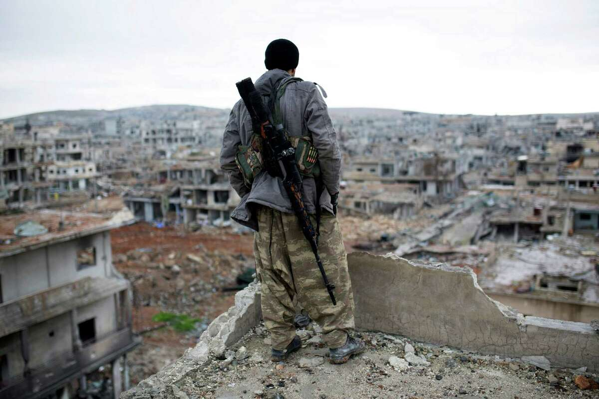 A sniper overlooks the remains of the city Ain al-Arab, also known as Kobani. Despite the Islamic State fighters' retreat, they promise not to be weakened, and that they will attack the city again.