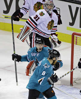Sharks right wing Melker Karlsson (68) celebrates with teammate Joe Pavelski (8) after scoring on Chicago goalie Antti Raanta (31) during the first period.