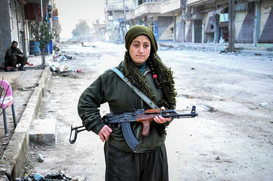 A member of Kurdish armed group stands guard among the wreckage left by fighting on a street in the center of the Syrian town of Kobani (Ayn al-Arab) on January 28, 2015 after it has been freed from Islamic State of Iraq and the Levant (ISIL) forces.Latest from AP: Islamic State fighters admit defeat in Syrian town of Kobani Photo: Anadolu Agency, Getty Images / 2015 Anadolu Agency