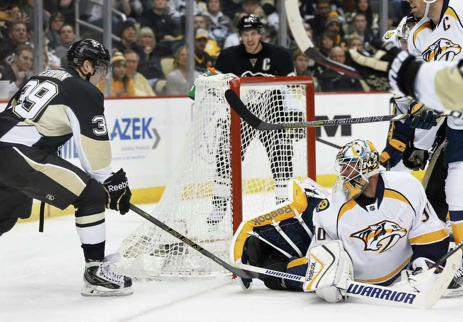 Pittsburgh Penguins' David Perron (39) tries to get to the puck as Nashville Predators goalie Carter Hutton (30) protects the net in the second period of an NHL hockey game, Sunday, Feb. 1, 2015 in Pittsburgh. (AP Photo/Keith Srakocic) ORG XMIT: PAKS110 Photo: Keith Srakocic / AP