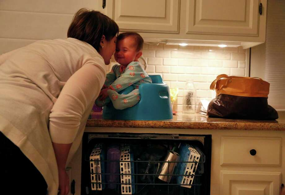Jennifer Simon shares a moment with her daughter Livia 6 mo., as she does the dishes at the Simon home Jan. 30, 2015 in Oakland, Calif. Livia, who is almost seven months and not old enough for a vaccine, was put in a 21 day quarantine after getting exposed to a child who had the measles at their pediatrician's office. Photo: Leah Millis / The Chronicle / ONLINE_YES