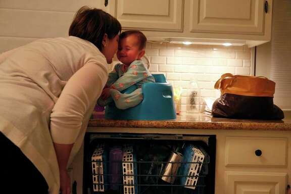 Jennifer Simon shares a moment with her daughter Livia 6 mo., as she does the dishes at the Simon home Jan. 30, 2015 in Oakland, Calif. Livia, who is almost seven months and not old enough for a vaccine, was put in a 21 day quarantine after getting exposed to a child who had the measles at their pediatrician's office.
