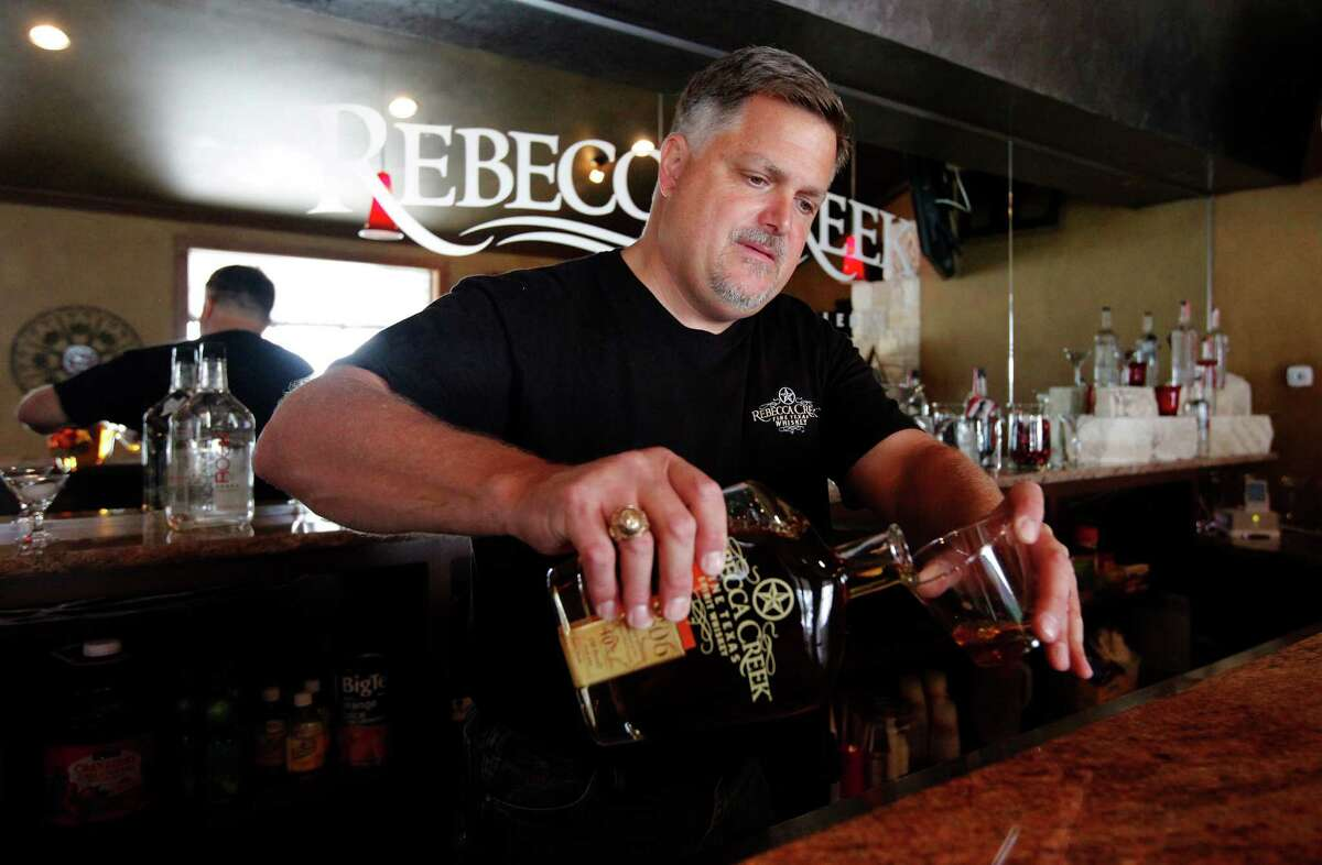 Rebecca Creek Distillery co-owner Mike Cameron pours a sample of whiskey in the tasting room.