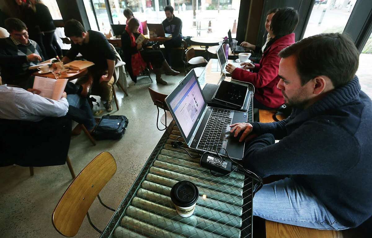Brian Bridger, right works on his laptop at Local Coffee at The Pearl