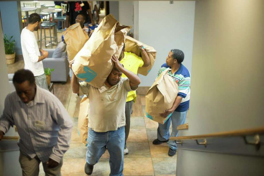 Volunteers bring in large bags of snacks during the Bread of Life ministry's annual Super Bowl party for the homeless Sunday. Photo: Jamaal Ellis, Freelance / ©2015 Houston Chronicle