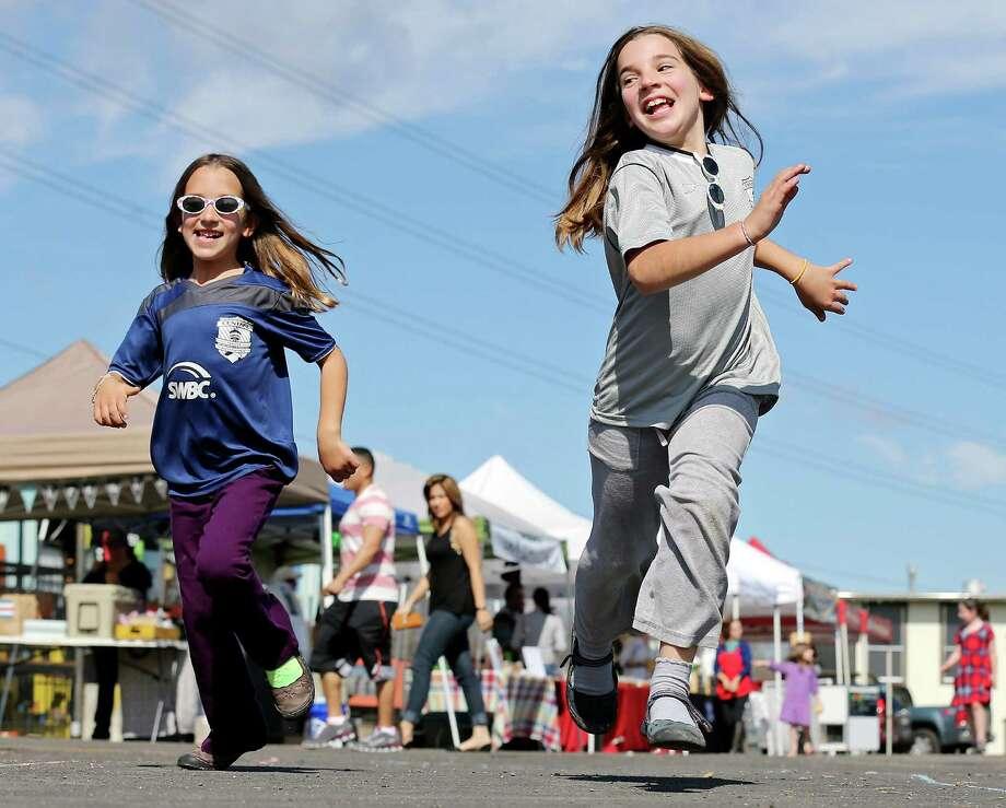 Enjoying the mild weather Sisters Sabine Carlson, 6, (left) and Savannah Carlson, 8, race at the Farmers & Ranchers Market at The Yard. Photo: Edward A. Ornelas /San Antonio Express-News / © 2015 San Antonio Express-News