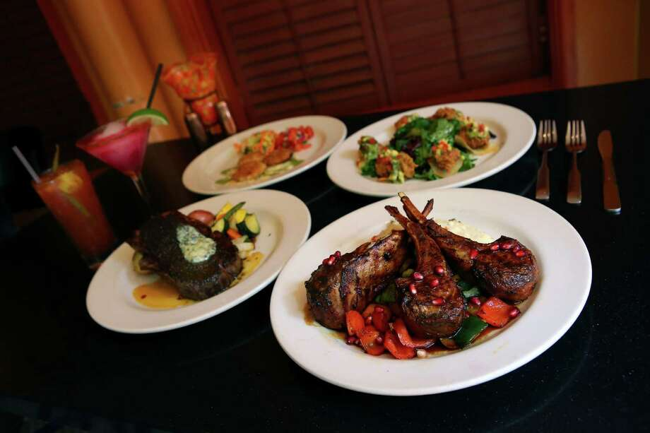 The achiote spiced double rib lamb chops, front, with the pink prickly pear margarita in the back. Photo: Express-News File Photo / © 2014 San Antonio Express-News