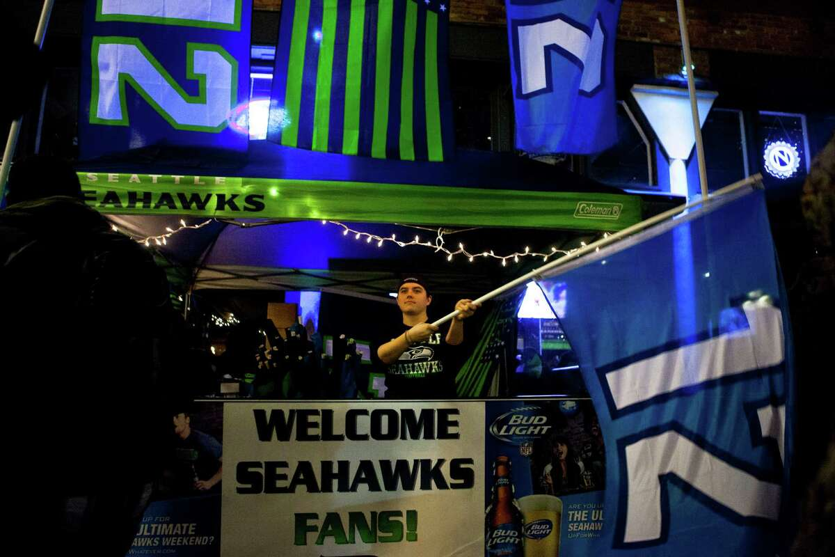 A Seahawks fan waves his 12 flag outside of the Box House Saloon after the Seahawks lost the Super Bowl to the Patriots 28-24.