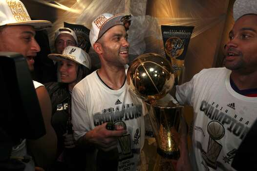 San Antonio Spurs' Tony Parker holds the Larry O'Brien NBA Championship trophy after defeating the Miami Heat at the AT&T Center, Sunday, June 15, 2014. Photo: Jerry Lara, San Antonio Express-News
