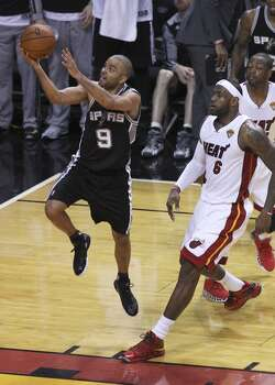 Spurs' Tony Parker (09) drives to the basket against Miami Heat's LeBron James (06) and Dwyane Wade (03) in the second half of Game 3 of the 2014 NBA Finals at the American Airlines Arena in Miami on Tuesday, June 10, 2014. (Kin Man Hui/San Antonio Express-News) Photo: Kin Man Hui, San Antonio Express-News