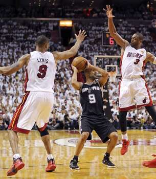 San Antonio Spurs' Tony Parker looks to pass between Miami Heat's Rashard Lewis and Dwyane Wade during Game 3 of the NBA Finals Tuesday June 10, 2014 at American Airlines Arena in Miami, Fla. Photo: Edward A. Ornelas, San Antonio Express-News