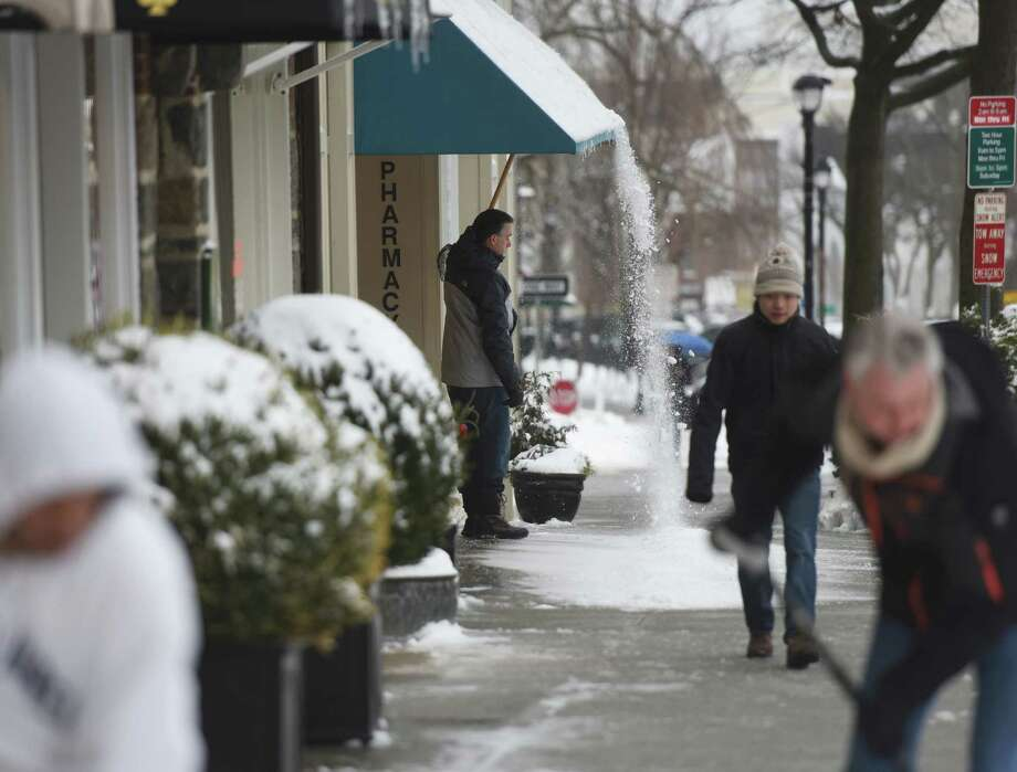 Evan Grannick, owner of Grannick's Pharmacy, clears snow off the overhang of his business as others dig out along Greenwich Avenue in downtown Greenwich, Conn. Monday, Feb. 2, 2015.  The area received about 6 inches of snow overnight and the storm is expected to continue throughout Monday with more snow and freezing rain possible. Photo: Tyler Sizemore / Greenwich Time