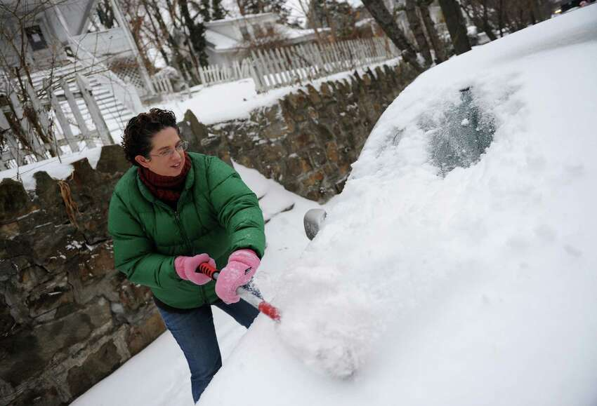 Jessica Hanbury clears snow off her car parked outside of her home in the Byram section of Greenwich, Conn. Monday, Feb. 2, 2015. The area received about 6 inches of snow overnight and the storm is expected to continue throughout Monday with more snow and freezing rain possible.