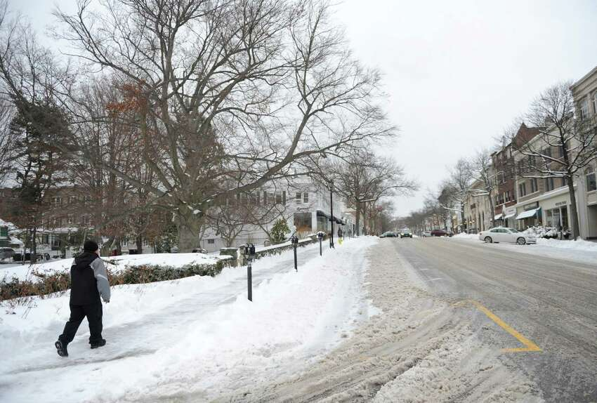 A man walks along the snow-covered Greenwich Avenue in downtown Greenwich, Conn. Monday, Feb. 2, 2015. The area received about 6 inches of snow overnight and the storm is expected to continue throughout Monday with more snow and freezing rain possible.