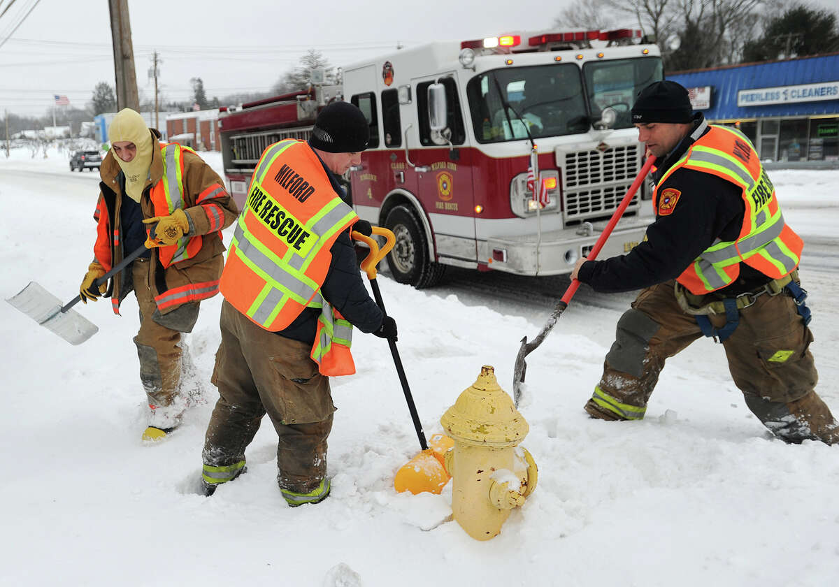 A Milford fire crew works its way up and down the Post Road clearing snow from around fire hydrants in the aftermath of the storm in Milford, Conn. on Monday, February 2, 2015.