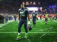Seahawks player Russell Okung walks off the field with teammates as celebrations begin for the New England Patriots during Super Bowl XLIX at University of Phoenix Stadium. The Seahawks lost to the Patriots 28 to 24. Photographed on Sunday, February 1, 2015.  (Joshua Trujillo, seattlepi.com)