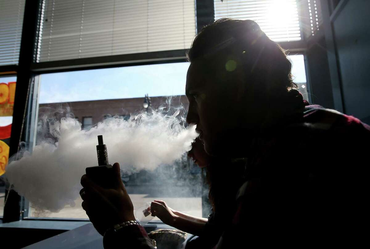 Kieran Thomas smokes an e-cigarette at Digita Ciggz in San Rafael. The California Department of Public Health released a report last week that calls e-cigarettes a public health threat and suggests that they should be regulated like regular cigarettes and tobacco products.