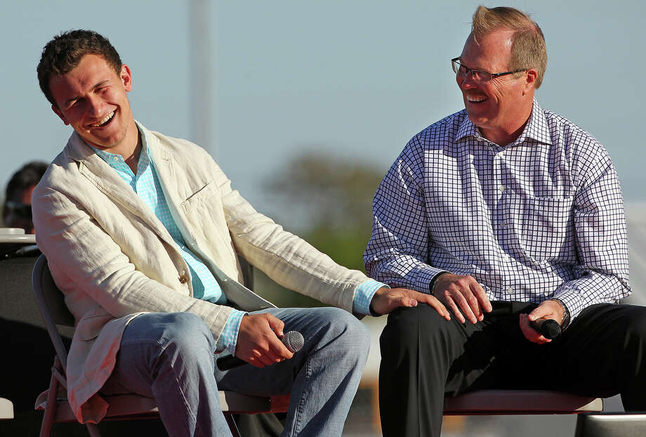 Johnny Manziel gets a laugh out of old stories from his high school coach at Kerrville Tivy, Mark Smith, during a homecoming rally for Manziel in Antler Stadium in Kerrville on April 20 2013. Photo: Tom Reel /San Antonio Express-News