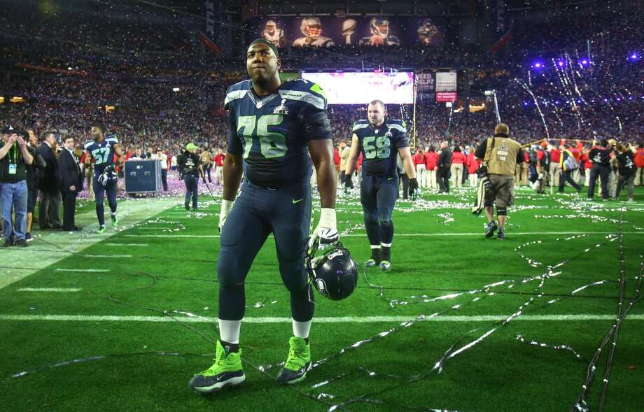Seahawks player Russell Okung walks off the field with teammates as celebrations begin for the New England Patriots during Super Bowl XLIX at University of Phoenix Stadium. The Seahawks lost to the Patriots 28 to 24. Photographed on Sunday, February 1, 2015.  (Joshua Trujillo, seattlepi.com) Photo: JOSHUA TRUJILLO, SEATTLEPI.COM