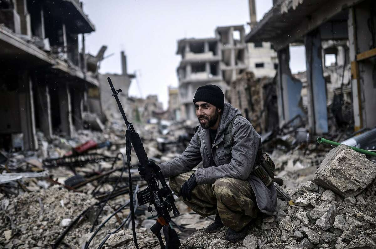 GHOST CITY: A 25-year-old Kurdish sniper named Musa takes a load off while scouting the destroyed Syrian town of Kobane, also known as Ain al-Arab. Kurdish forces recaptured the town on the Turkish frontier in a symbolic blow to the Islamic State jihadists.