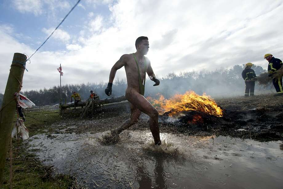 """WHEN THE GOING GETS TOUGH, THE TOUGH TAKE OFF THEIR PANTS:A competitor runs through an puddle in the """"Tough Guy"""" adventure race near Wolverhampton, Staffordshire, West Midlands. The event challenges thousands of tough guys to run through a grueling 200 obstacles, including water, fire and tunnels after a lengthy run at the start. Photo: Oli Scarff, AFP / Getty Images"""