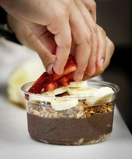 Angel Serratos of Bowl'd Acai makes an Original Gangsta — a base of acai pulp with frozen fruit and coconut water topped with granola, sliced fruit, flaked coconut and a drizzle of honey. Photo: Russell Yip / The Chronicle / ONLINE_YES