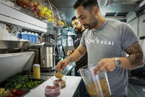 Reza Morvari (foreground) and Angel Serratos of Bowl'd Acai work in their food truck at Mint Plaza in downtown S.F.