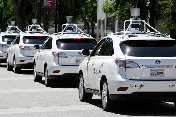 A row of Google self-driving cars line up outside the Computer History Museum in Mountain View. Some drivers like the technology.