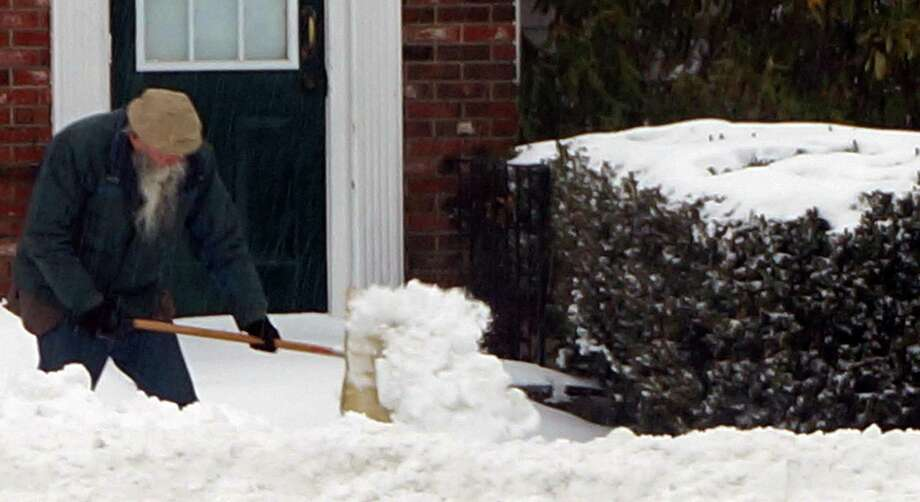A man, in compliance with a town ordinance clearing property owners to clear public sidewalks after a storm, on Monday shovels a sidewalk on Reef Road. Photo: Genevieve Reilly / Fairfield Citizen