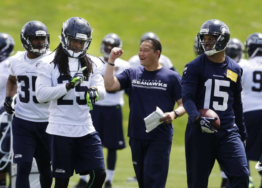 Seahawks' defensive passing game coordinator Rocky Seto, center, reacts after cornerback Richard Sherman intercepted a pass during Seahawks OTAs, Tuesday, May 27, 2014, in Renton, Wash. Photo: Ted S. Warren, Associated Press