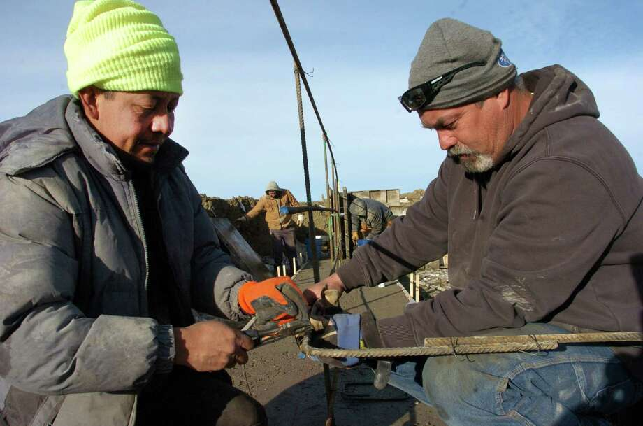"In this Thursday, Jan. 15, 2015, photo, Efren Hernandez, left, and Kyle Bockin work on the foundation of an apartment complex under construction on the outskirts of Watford City, North Dakota. Developers are building thousands of housing units in Watford as an alternative to the ramshackle ""man-camps"" used by many oil field workers. (AP Photo/Matthew Brown) ORG XMIT: RPMB106 Photo: Matthew Brown / AP"