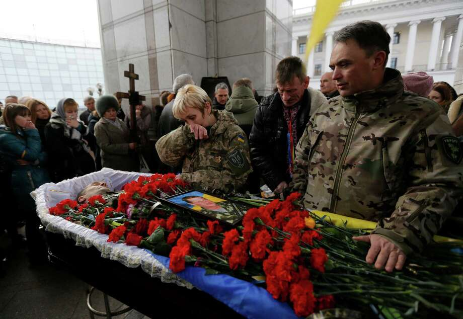 People pay their final respects to Ruslan Baburov who was killed in fighting against Russian-backed separatists, during a commemoration ceremony in Independence Square in Kiev, Ukraine, on Monday, Feb. 2, 2015. Ukraine's government said Sunday that 13 of its troops were killed and another 20 wounded in a day of fighting across the east. (AP Photo/Sergei Chuzavkov) ORG XMIT: XSC106 Photo: Sergei Chuzavkov / AP