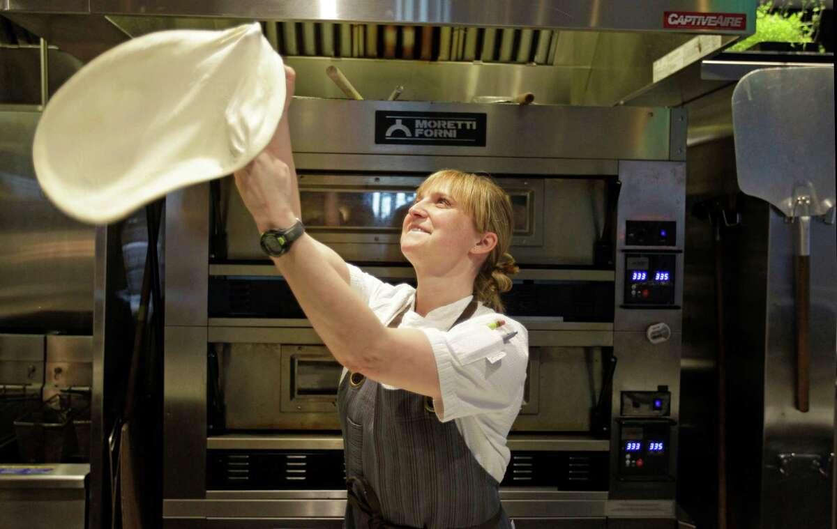 Chef Erin Smith tosses pizza dough.