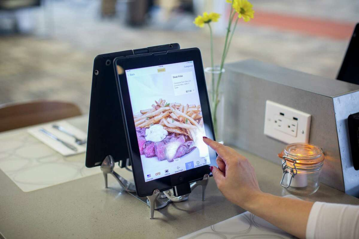 A traveler browses one of the iPads that sit at every table in the Mimosa restaurant in Terminal 1 at the Minneapolis-Saint Paul International Airport.