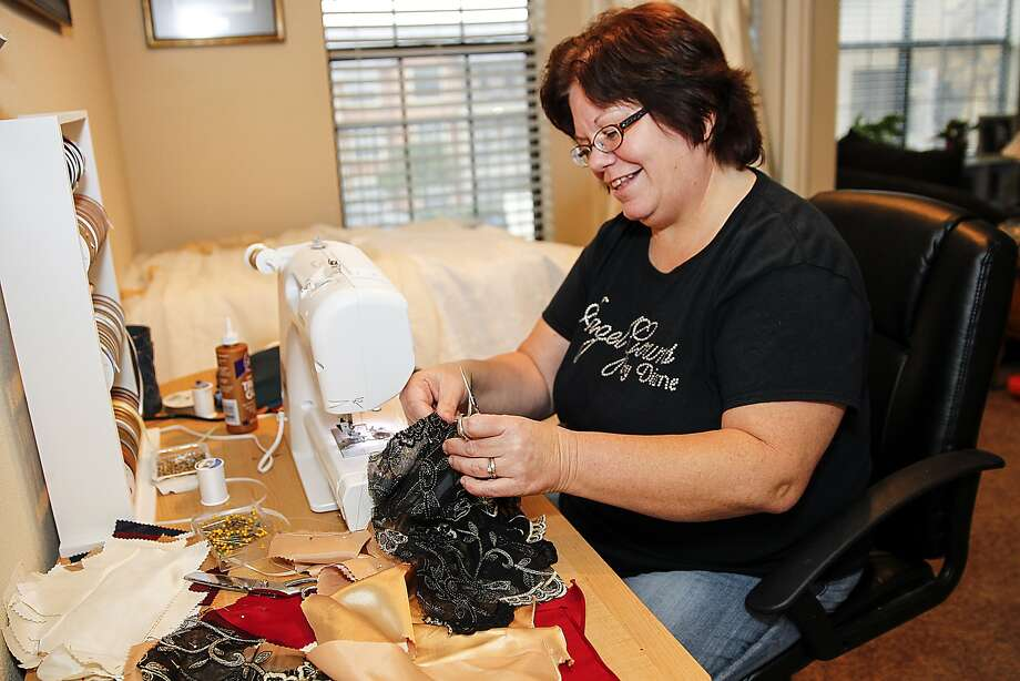Diane Dionne sits at her sewing machine in Katy removing embellishments from a donated formal dress to use on one of her Angel gowns, burial clothes for babies. Diane Dionne sits at her sewing machine in Katy removing embellishments from a donated formal dress to use on one of her Angel gowns, burial clothes for babies. Photo: Diana L. Porter, Freelance / © Diana L. Porter