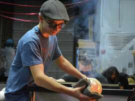 Theoren Hanks, 14, a former student at Public Glass, works on a piece at Area 253 Glassblowing in Tacoma, Wash.
