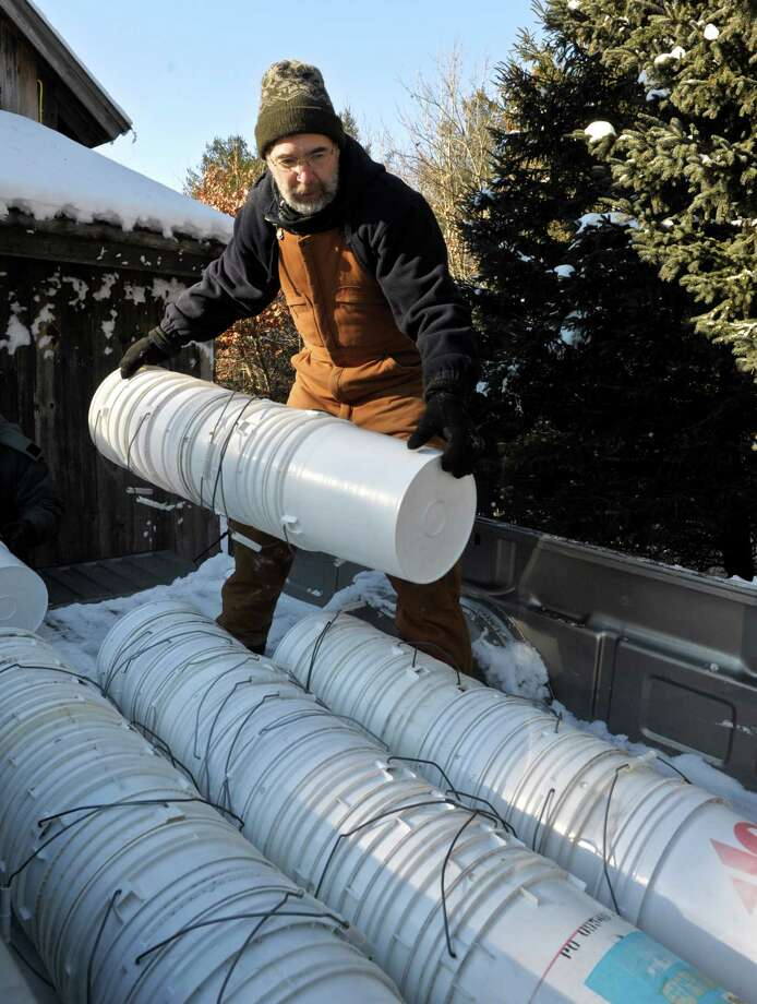 Harry Gerowe stacks buckets, used to collect sap from the sugar maple trees at Flanders Nature Center, in the back of a pickup. Gerowe has been volunteering to help with the maple sugaring at the center for over a 20 years. Volunteers showed up, with the temperature still in the teens, to place taps in the sugar maple trees that surround South Field, and hang buckets to collect their sap, on Saturday, January 31, 2015, in Woodbury, Conn. Photo: H John Voorhees III / The News-Times