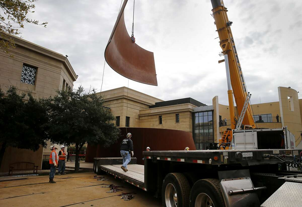 """A large crane brings a piece of the metal sculpture over to al waiting truck Tuesday January 27, 2015. A huge Richard Serra sculpture called """"Sequence"""" is removed from Cantor Arts Center on the Stanford University campus for later installation at SFMOMA."""