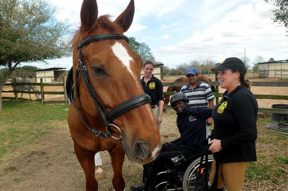 """Derrick Perkins, center, of Sugarland, visits with Snowdonia Farms owner and trainer Jayne Lloyd, from right, Barn Manager Felix Alonzo, and Asst. Instructor/Trainer Jessica Little after Perkins training session on """"Joshua"""", a 12 yr. old Hannoverian, at the equestrian center in Tomball on Jan. 29. Photo: Jerry Baker, Freelance"""