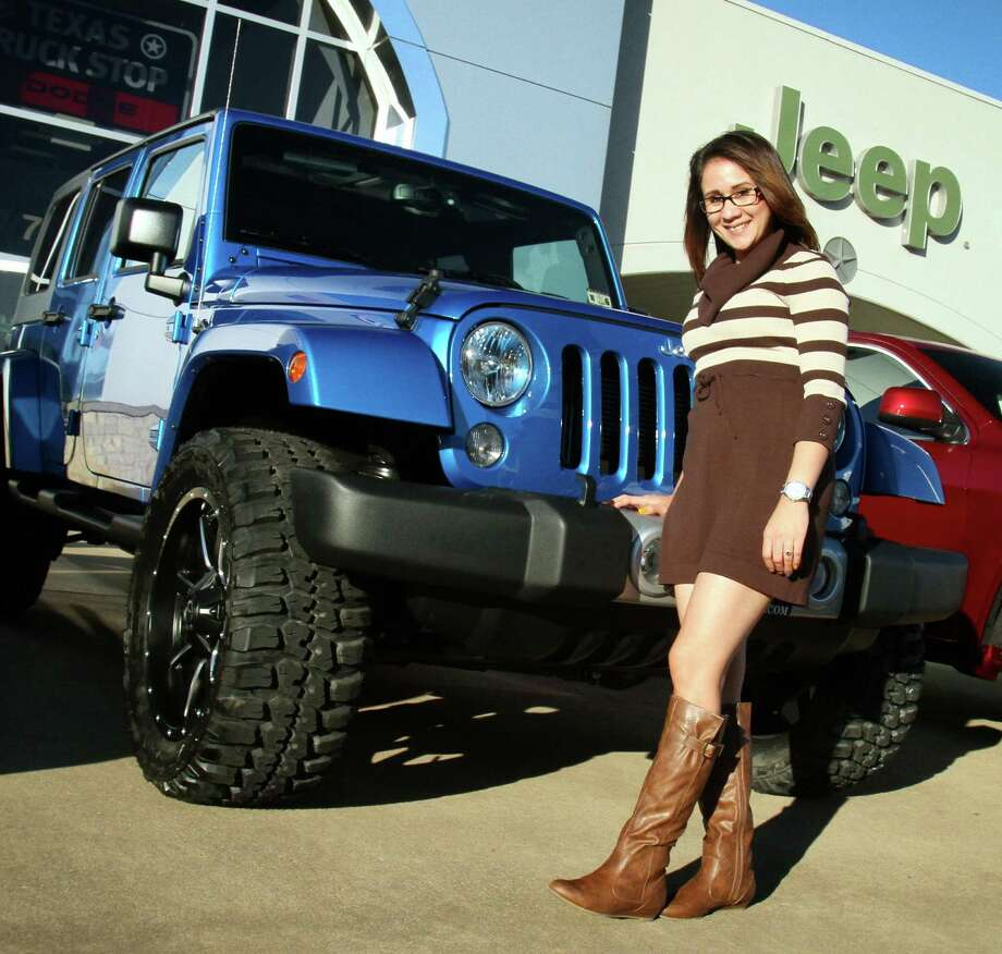 The four-door Wrangler opened the door to much of the Jeep brand's resurgence in recent years. Savannah Martinez, aftermarket manager at Helfman Dodge Chrysler Jeep Ram, shows the 2.5-inch lift treatment and 33-inch tires that have been a hit with Wranger buyers. Photo: Jeffrey Yip / (c) Jeffrey Yip 2014