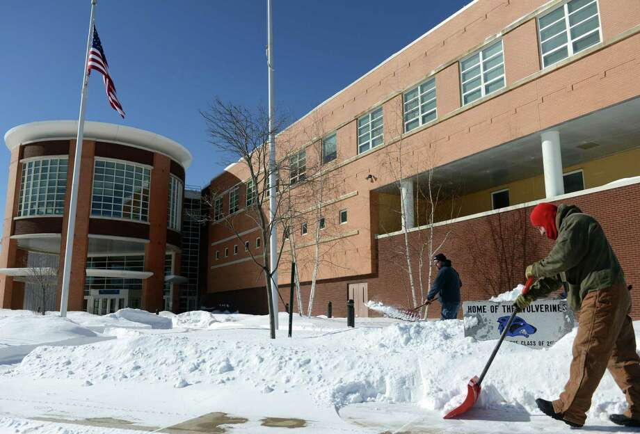School employees Peter Szkurat, front, and Paul Mirabelle clear snow from the walkways around Oxford High School Tuesday, Feb. 3, 2015 following Monday's storm which closed school for Monday and Tuesday. Photo: Autumn Driscoll / Connecticut Post