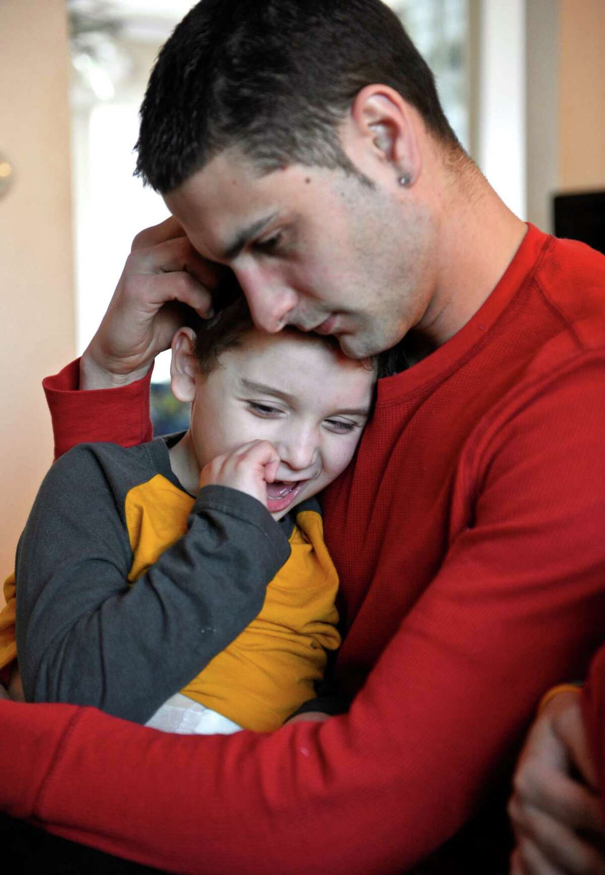 Jayce Correia sits with his son Jared Carreras, 8, in their Brookfield, Conn, home, on Tuesday, February 3, 2015. Correia made a video, of a rap song he composed, with Jared and uploaded it to YouTube, it has had over 500,000 hits. Jared was born with cerebral palsy, hydrocephalus, epilepsy, and several other debilitating medical conditions as a result of a stroke he suffered in utero. His parents feel that although Jared can't stand, walk, talk or see, he is a
