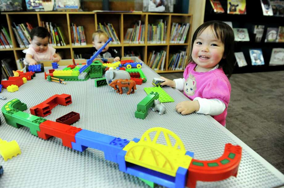 Nene Kaneko, 20 months, of Watervliet, right, plays at the Lego table during the grand opening of the Youth Services Room on Tuesday, Feb. 3, 2015, at Albany Public Library in Albany, N.Y. (Cindy Schultz / Times Union) Photo: Cindy Schultz / 00030307A