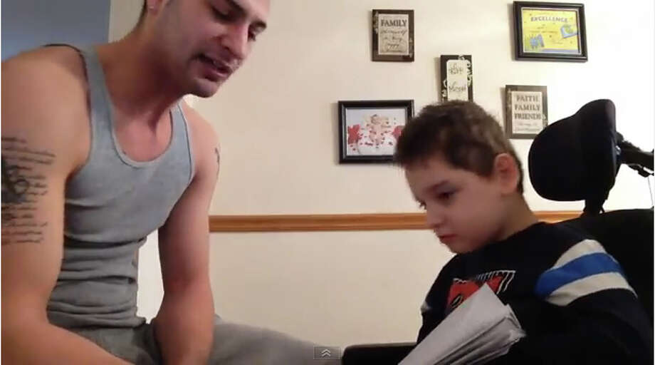 This is from a video clip of of Jayce Correia, left, and his son Jared, 8. Correia made a video of a rap song he composed with Jared and uploaded to YouTube. Photo: Contributed Photo / The News-Times Contributed
