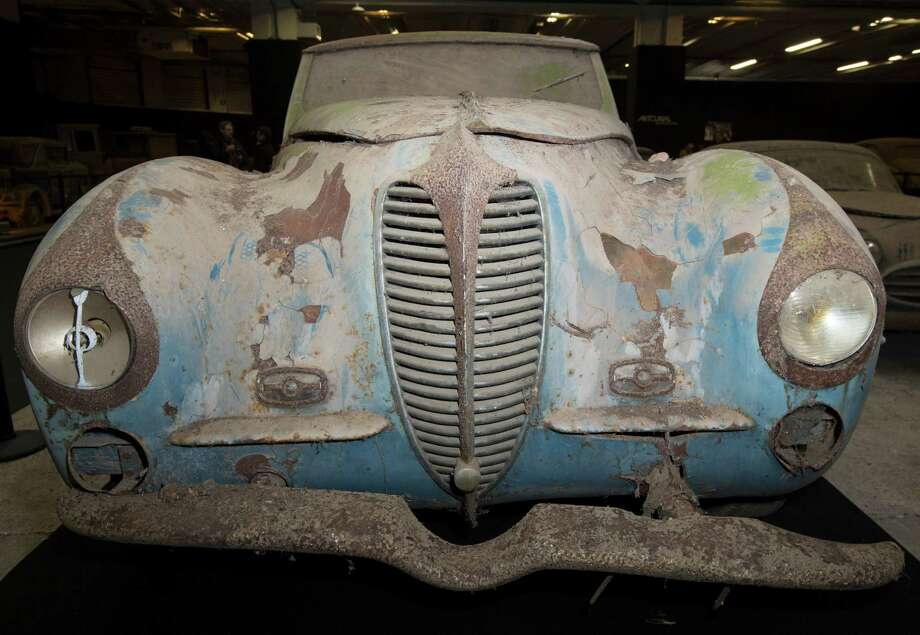 A Delahaye 135-M cabriolet Faget-Varnet is displayed during a preview for an auction of vintage cars Retromobile show in Paris, Tuesday, Feb. 3, 2015, after a treasure trove of classic cars was discovered after spending 50-years languishing in storage on a farm.  60 rusting motors, which include a vintage Ferrari California Spider, a Bugatti and a very rare Maserati, were found gathering dust and hidden under piles of newspapers in garages and outbuildings at a property in France.  The cars were collected from the 1950s to the 1970s by entrepreneur Roger Baillon, who dreamt of restoring them to their former glory and displaying them in a museum, but, his plans were dashed as his business struggled, forcing the sale of about 50 vehicles, to be auctioned off on Feb. 6. Photo: Jacques Brinon, Associated Press / AP