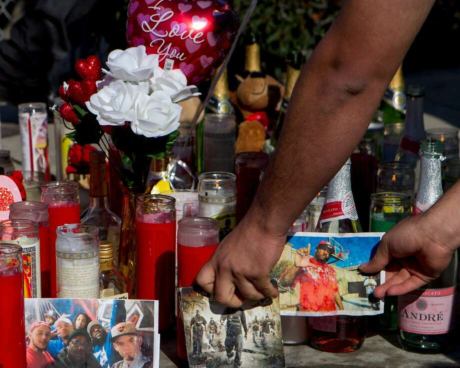 """Alex Montano straightens out a photo of Dominic Newton, 37, at the site of the incident near 94th Avenue and MacArthur Boulevard, Tuesday, Feb. 3, 2015, in Oakland, Calif. Newton was a Bay Area rapper known by his stage name """"The Jacka"""" who was shot and killed Monday night. Photo: Santiago Mejia, The Chronicle"""
