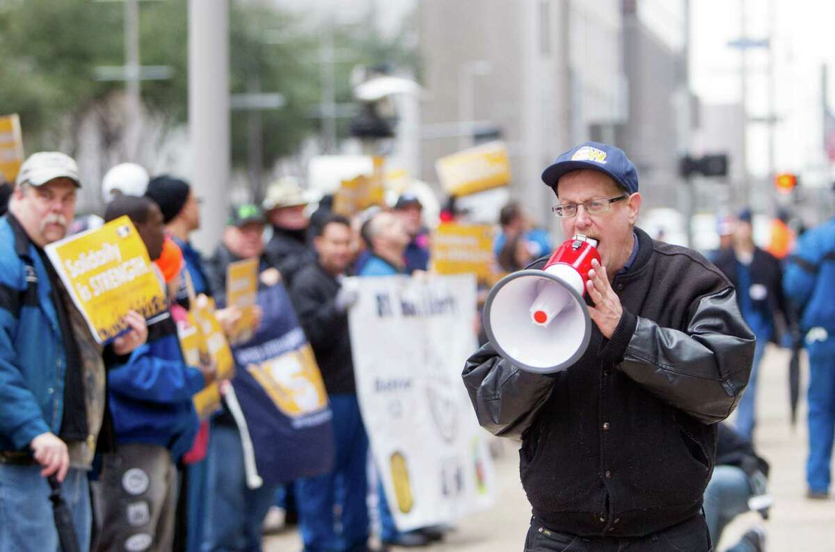 """Mike Zielinski leads United Steelworkers union members as they picket in front of the LyondellBasell Tower, Tuesday, Feb. 3, 2015, in Houston. Union officials say it's the first time that refinery workers picketed the corporate offices. A line of men and women marched up and down the McKinney street headquarters carrying signs, including a large banner demanding an end to """"the assault on American workers."""" (Cody Duty / Houston Chronicle)"""