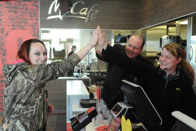 Ivy Brown of Waterford, left, gives owner/operator Roger Grout and shift manager Angella Manella a high five in exchange for paying for her order as part of the a€œLovina€™ Acta€ campaign at McDonald's on Tuesday Feb. 3, 2015 in Waterford, N.Y. McDonalda€™s is now accepting Lovina€™ as a form of currency. With the launch of McDonalda€™s a€œPay with Lovina€™a€ Super Bowl commercial, the company is bringing the idea to life at participating restaurants across the U.S. Some lucky customers in the New York Capital Region as well as restaurants in the Berkshires of Massachusetts and select regions in Western Vermont, will be selected through a randomized process at predetermined times and engaged to pay with a Lovina€™ act instead of money. (Michael P. Farrell/Times Union) Photo: Michael P. Farrell / 00030430A