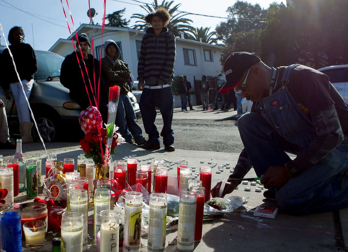 """Steve Wilson (right) lights a candle in memorial for Dominic Newton, 37, at the site of the incident near 94th Avenue and MacArthur Boulevard, Tuesday, Feb. 3, 2015, in Oakland, Calif. Newton was a Bay Area rapper known by his stage name """"The Jacka"""" who was shot and killed Wednesday night."""