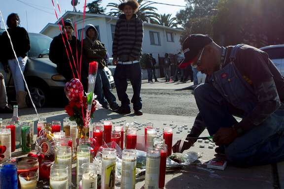 "Steve Wilson (right) lights a candle in memorial for Dominic Newton, 37, at the site of the incident near 94th Avenue and MacArthur Boulevard, Tuesday, Feb. 3, 2015, in Oakland, Calif. Newton was a Bay Area rapper known by his stage name ""The Jacka"" who was shot and killed Wednesday night."